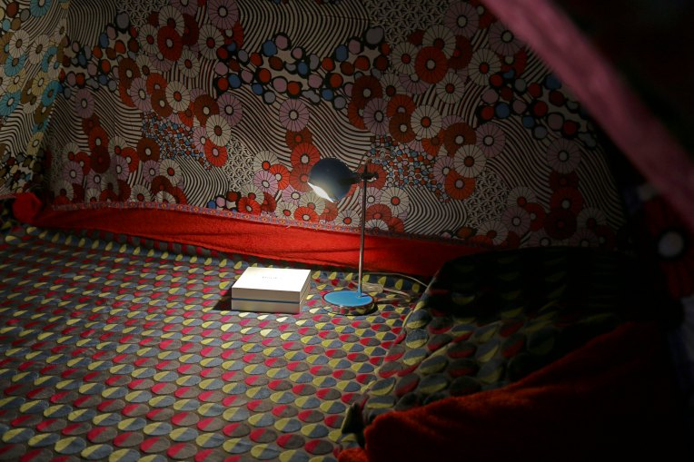 tent interior, book box and lamp